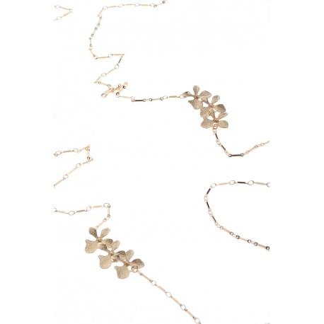 <p>Collar extra largo (130cm aprox.) con cadena y flores chapadas en oro de 18k, adornado con una mini calavera de hueso blanco.</p>