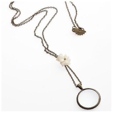 <p>Collar con cadena de latón en oro envejecido, con flor de nacar y lupa pequeña a modo de charm (diámetro de 2 cm)<br />Largo aproximado: 45 cm</p>