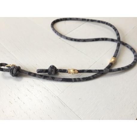 <p><span>Práctico collar para cualquier tipo de gafa.</span><br /><br /><span>Cordón de piel de ante con print de leopardo gris, de 4mm de grosor,y adorno de cabezas de serpiente chapadas en oro de 18k.</span><br /><br /><span>Largo aproximado: 88cm</span><br /><br /><span>Disponible en más colores. Disponible también chapado en plata de ley.¡Consúltanos!</span></p>